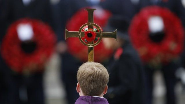 Boy holds cross at Cenotaph