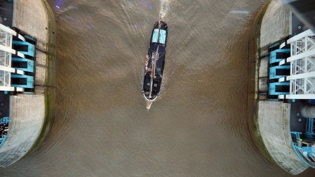A tall ship passes under the newly installed glass floor 138 feet above the River Thames at Tower Bridge