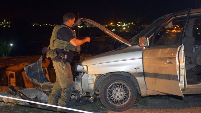 An Israeli soldier inspects a vehicle at the scene of an attack near the West Bank Jewish settlement of Alon Shvut