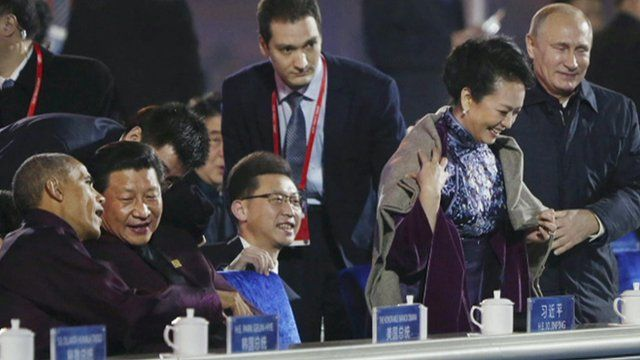 Vladimir Putin putting a shawl around Peng Liyuan while seated alongside Xi Jinping and Barack Obama