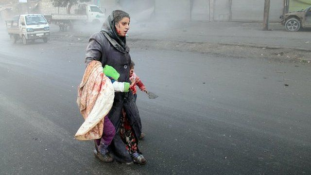 A wounded Syrian woman walks with her children in Aleppo, northern Syria, 15 December 2013