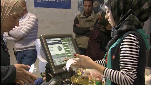 A shopper and cashier at a supermarket in Syrian refugee camp