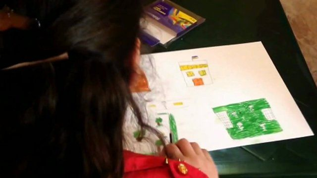 A Syrian child refugee draws a picture of her home