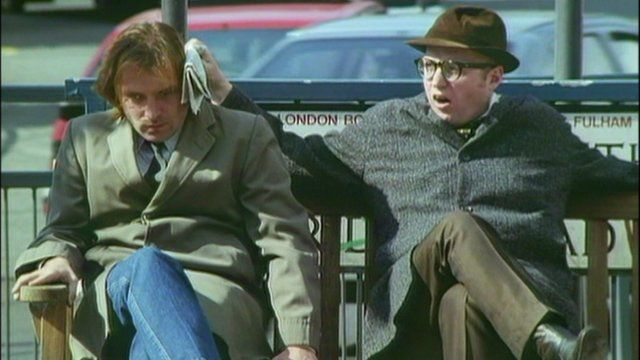 Rik Mayall and Adrian Edmondson sitting outside on the bench in the opening credits of the sitcom Bottom