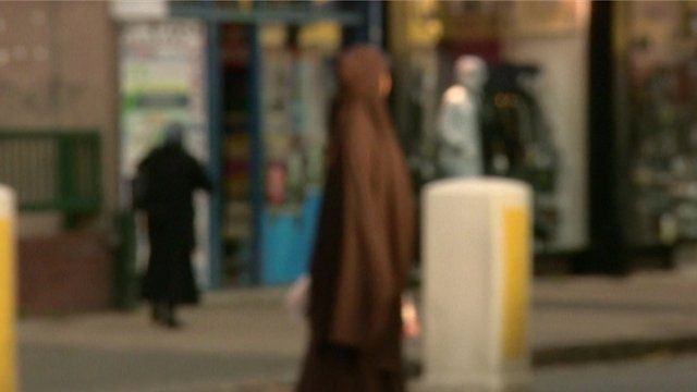A veiled woman crossing the street.