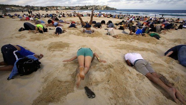 A group of around 400 demonstrators participate in a protest by burying their heads in the sand at Sydney's Bondi Beach