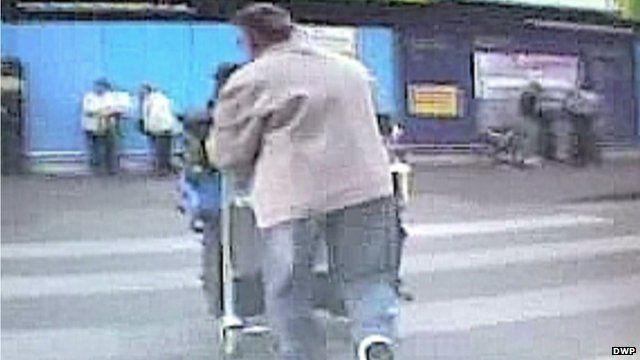 Samuel Bennett walking and pushing luggage into Manchester Airport