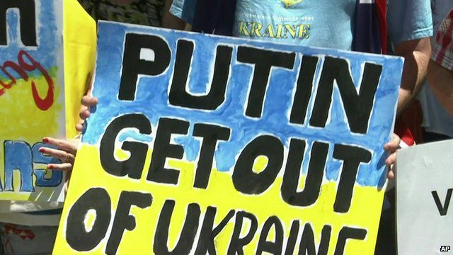 Close up of G20 anti-Putin protester holding banner saying 'Putin Get out of Ukraine'