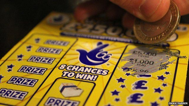 Close up of someone using a two-pound coin on a National Lottery scratchcard