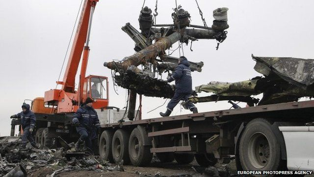 Workers remove wreckage from the MH17 crash site
