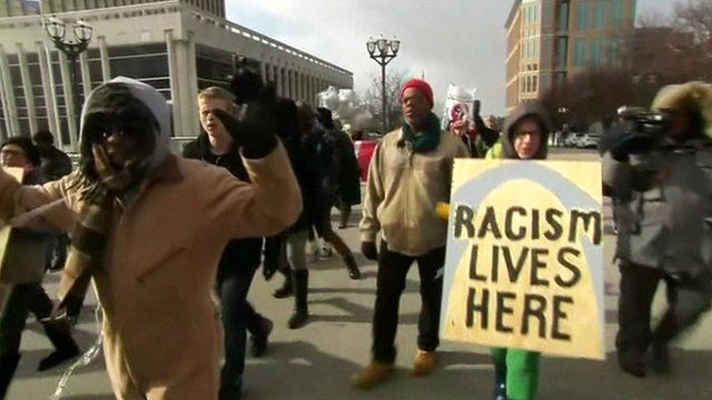 Protesters in St Louis including one with a placard reading 'Racism lives here' written on top of a picture of the Gateway Arch