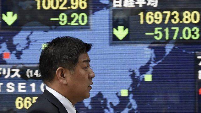 A pedestrian walks past a stock market board