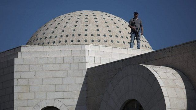 Police stand guard on a roof of synagogue