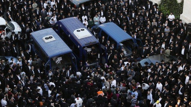 Ultra-Orthodox Jews mourn three of the victims of an attack on a Jerusalem synagogue