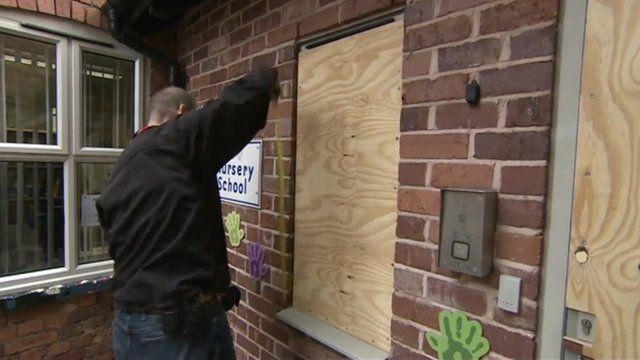 A workman boards up a broken window