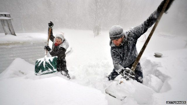 Two people shovelling snow