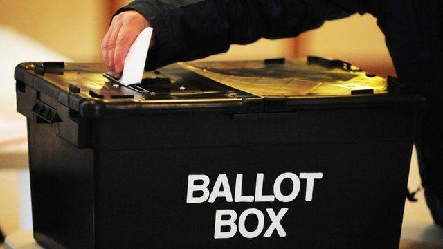 Person putting voting slip into ballot box