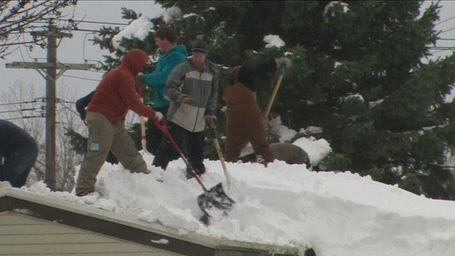 People clearing snow from a roof
