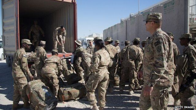 US Army guardsmen load a lorry with their luggage as they leave at the end of their tour at Kandahar airfield, 14 November 2014