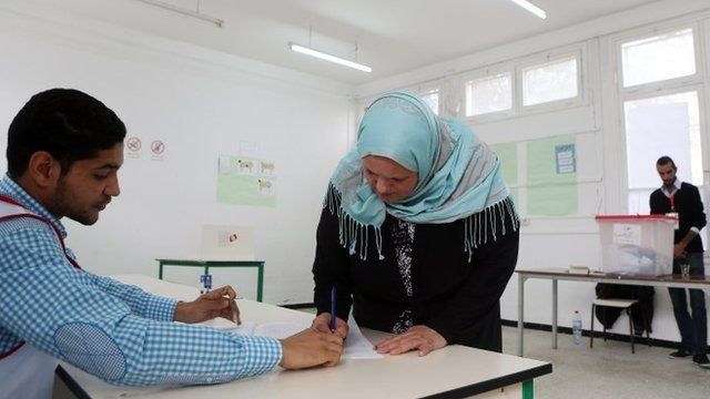 Tunisian woman collects ballot paper