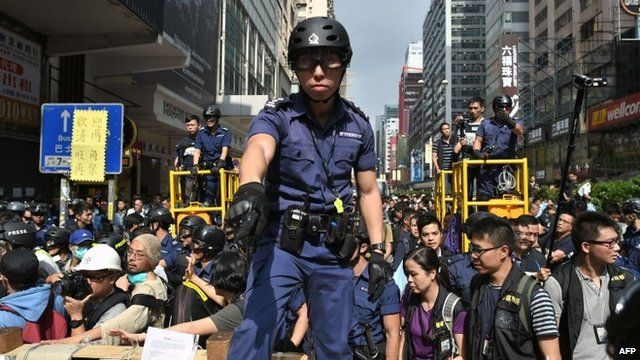 Police officer standing on barricade in Mong Kok district