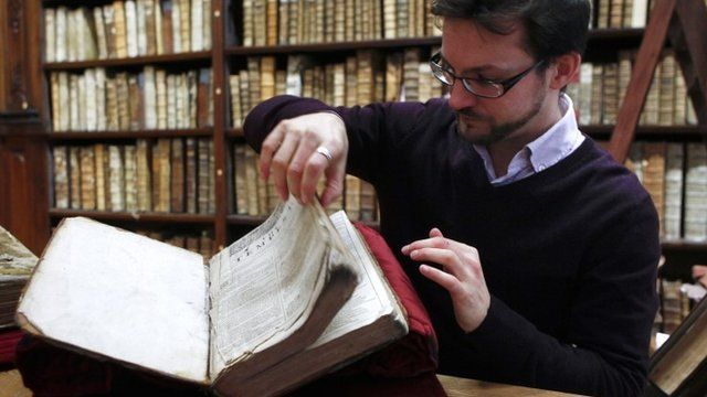 """Remy Cordonnier, the director of the Saint-Omer library's medieval and early modern collection, opens a page of the newly discovered Shakespeare""""s original first folio."""