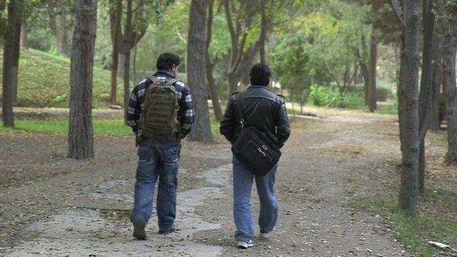 Two interpreters walking in park in Kabul