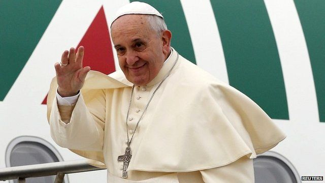Pope Francis waves as he boards a plane in Rome heading to Turkey