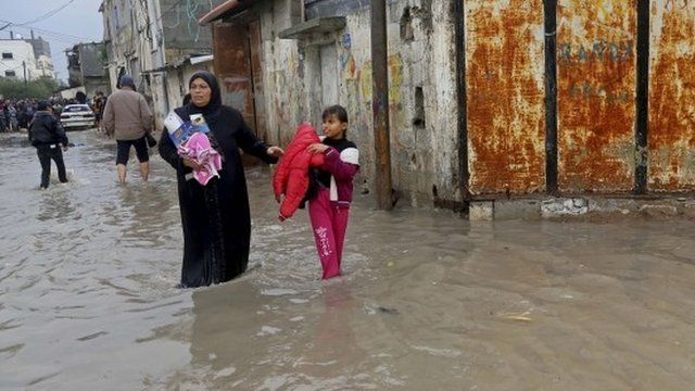 A Palestinian woman and her daughter carry their belongings from their flooded family house
