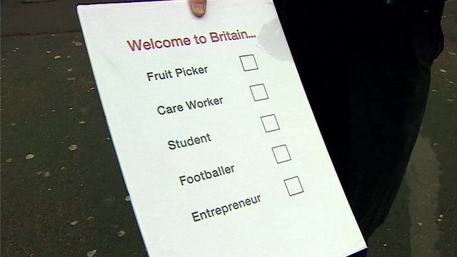 Close up of reporter holding list of 5 professions under headline 'Welcome to Britain ...'
