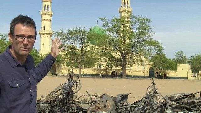 Will Ross pointing at mosque with pile of twisted metal in front of it