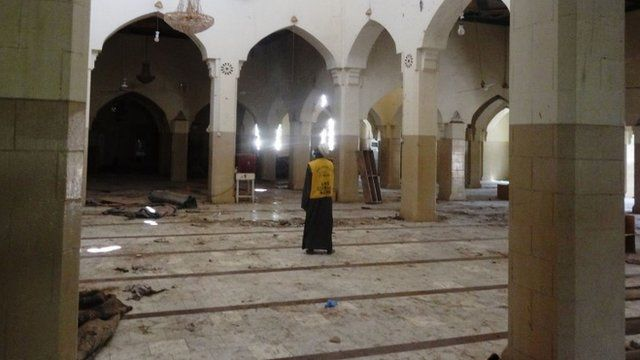 "A mosque official surveys damage in the central mosque in northern Nigeria""s largest city of Kano on November 29, 2014"
