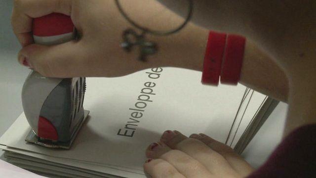 Woman stamping voting envelope