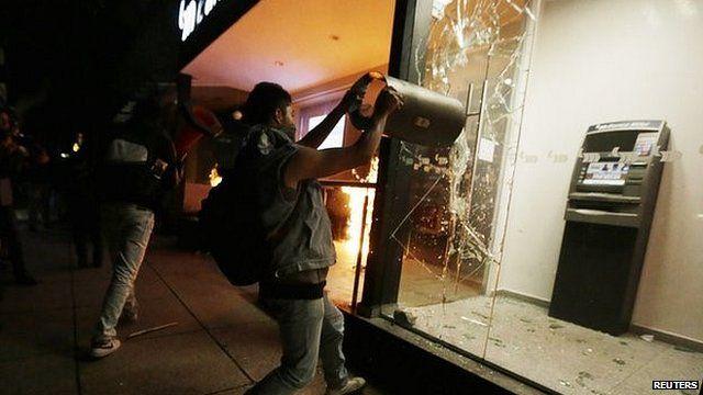 A demonstrator breaks the window of an ATM machine