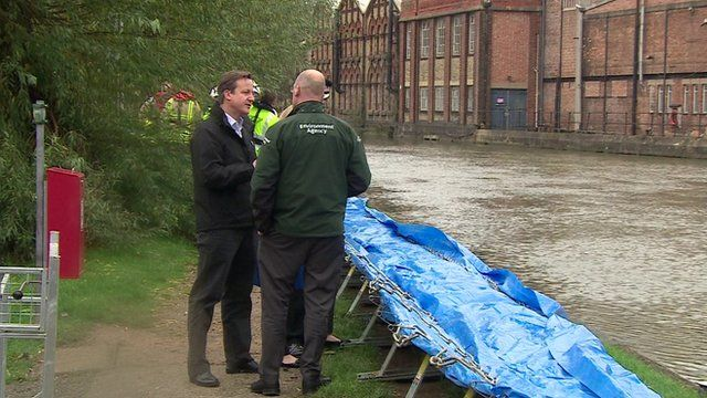 David Cameron examining flood defences