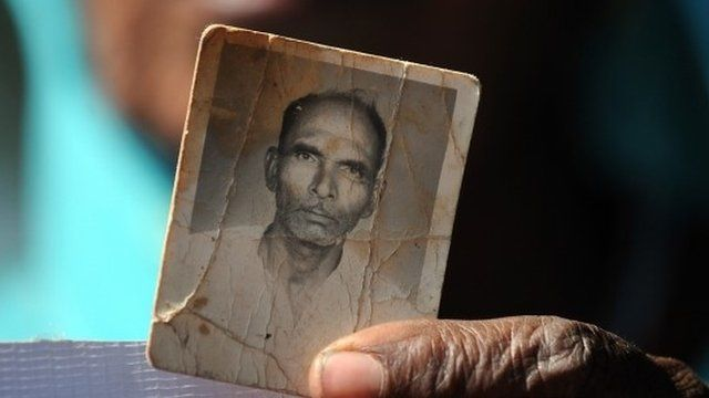 A Bhopal poison gas disaster victim holds a frayed photograph of her late husband during a protest rally in Bhopal