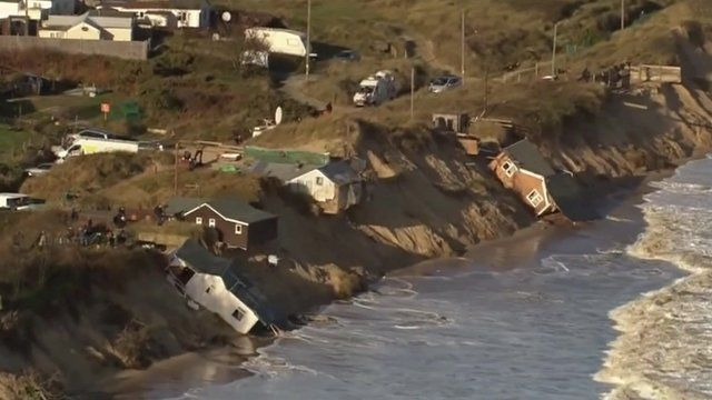 Homes slide into the sea after last year's tidal surge