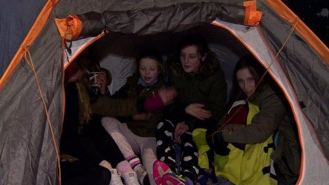 Young fans camp out in Belfast City centre in the hope of securing One Direction tickets, as BBC Newsline's Andy West reports