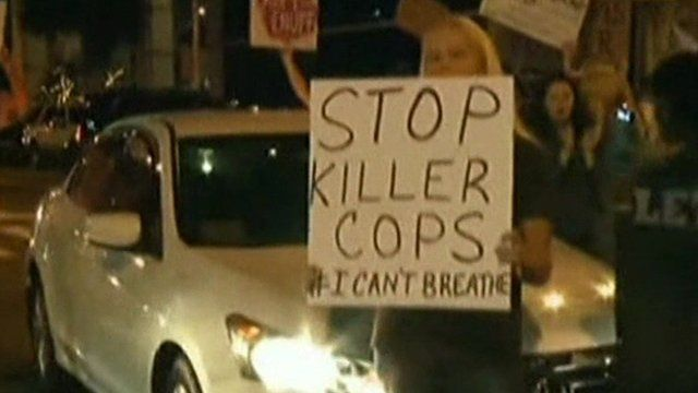 A protester holding a sign reading 'Stop killer cops'