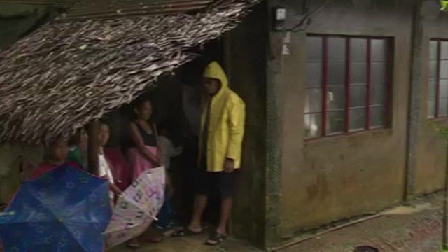 Family sheltering under thatched roof