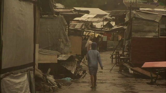 A child walking down a street between some ramshackle shelters in Tacloban