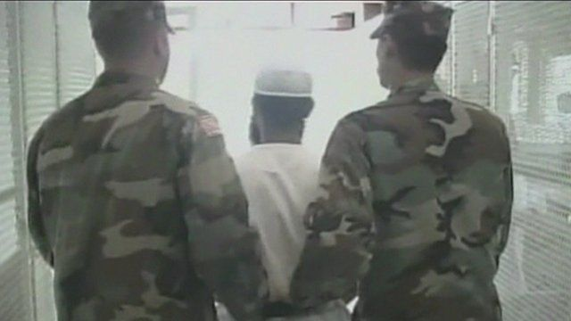 A prisoner being led away by two guards