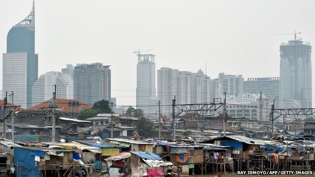 Shanty houses on a river bank in Jakarta, in shadow of skyscrapers