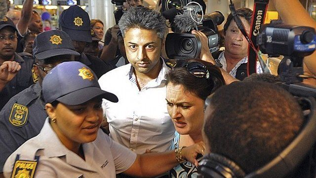 Shrien Dewani flanked by police, walking through the airport