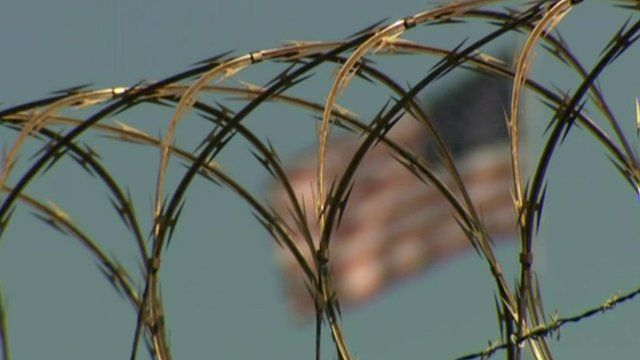 Barbed wire with flag in the background