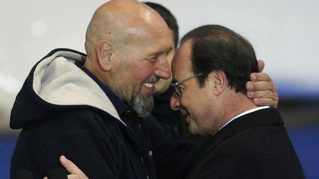 Serge Lazarevic (L) hugs French President Francois Hollande after he arrives at Villacoublay military airport (10 Dec)