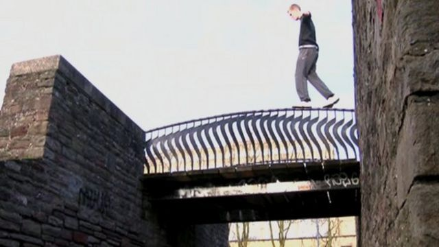 James Rudge walking on the barrier of a bridge