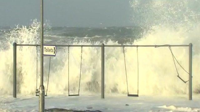 Waves crash over wall by playground swings