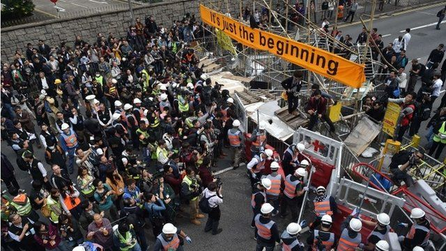 Members of the media and bystanders (L) look on as authorities (C) dismantle a barricade