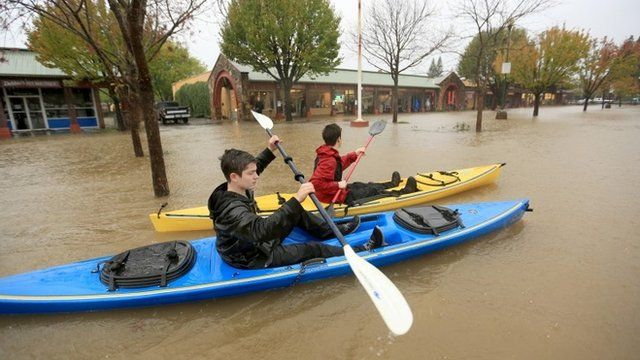 Two boys kayak through floodwaters in the Healdsburg Center parking lot